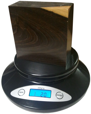 A piece of Lignum Vitae is weighed on a small digital scale.